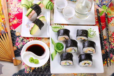 sake maki: japanese maki sushi rolls set with salmon and avocado and sake