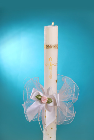 white candle for the first holy communion on blue background