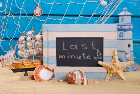 last minute: seaside background and marine wooden frame with last minute offer written on blackboard standing on beach sand