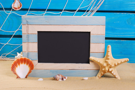 seaside background and marine wooden frame with blackboard standing on beach sand photo