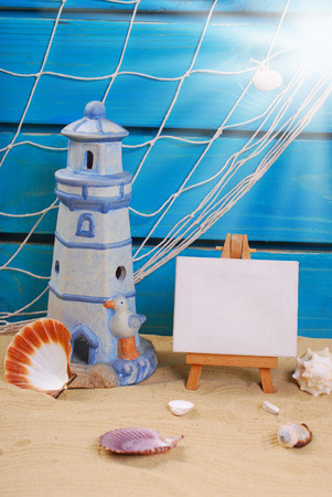 fish net: seaside summer holidays still life with lighthouse,fish net on blue wooden background ,shells and small easel to write text standing on the beach sand