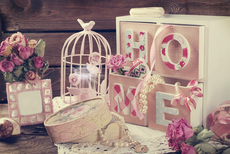 Vintage home still life with wooden drawers boxpink cage and photo frame in romantic style Stockfoto