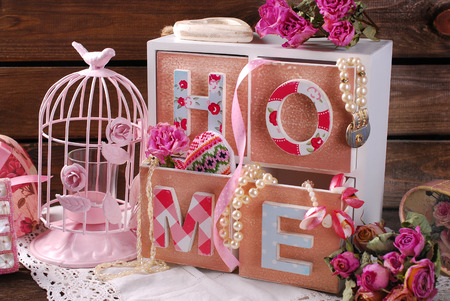 Vintage home still life with wooden drawers boxpink cage and dried roses in romantic style photo