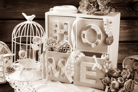 home accessories: vintage sepia home still life with wooden drawers boxmetal cage and dried roses in romantic style