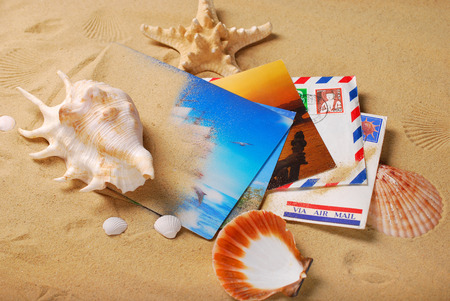cartas antiguas: old letters and postcards from summer vacations lying on sand with shells