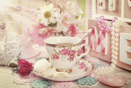 pearl tea: tea in fine china cup with roses ornament and anise meringue cookies in romantic vintage style Stock Photo