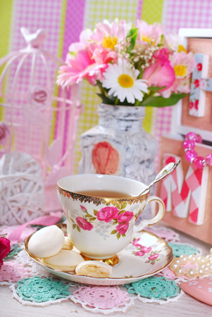 fine china: tea in fine china cup with roses ornament and anise meringue cookies in romantic style