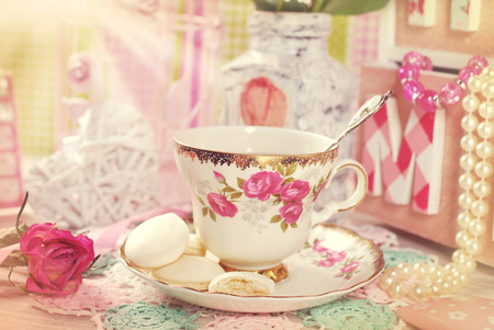 fine china: tea in fine china cup with roses ornament and anise meringue cookies in romantic vintage style Stock Photo
