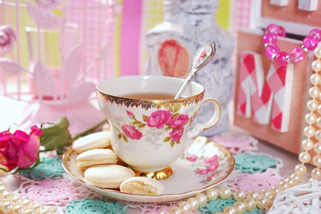 china rose: tea in fine china cup with roses ornament and anise meringue cookies in romantic style