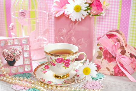 china rose: tea in fine china cup with roses ornament  in romantic style Stock Photo