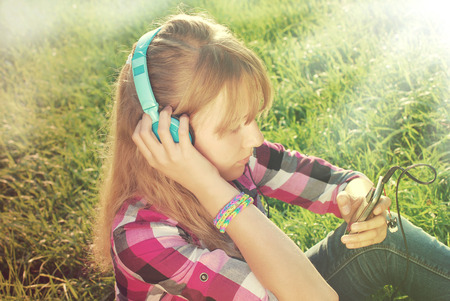 young beautiful girl with headphones on ears listening music in smartphone on the meadow in vintage style photo
