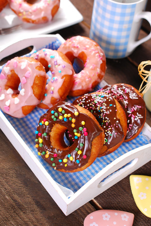 homemade donuts with chocolate and icing glaze and colorful sugar sprinkles on wooden table photo