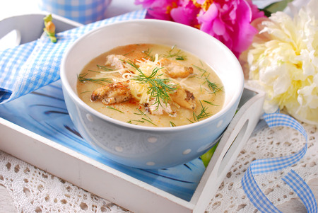 a bowl of cauliflower cream soup with grilled cheese and dill chickenparmesan in wooden tray photo