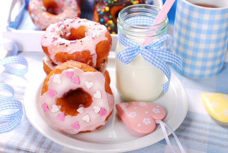 icing sugar: homemade donuts with icing sugar glaze and colorful sprinkles and milk in bottle