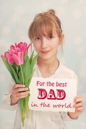 beautiful young girl giving bouquet of pink tulips and greeting card for dad on fathers day photo