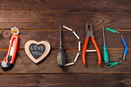 kid's day: text I love you dad made with DIY tools on wooden background for fathers day