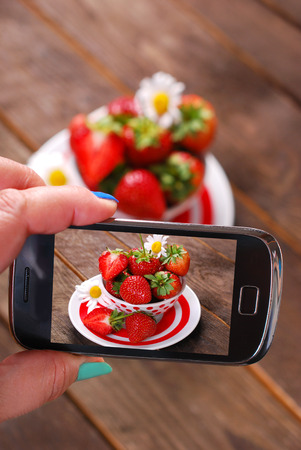 photographing: hand holding smartphone and taking photo of fresh strawberries in bowl on wooden rustic table Stock Photo