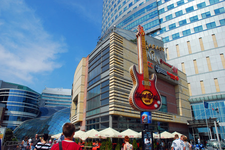 complex: WARSAW,POLAND-AUGUST 11,2014:famous guitar-symbol of Hard Rock Cafe in the center of Warsaw and shopping mall Golden Terraces Editorial