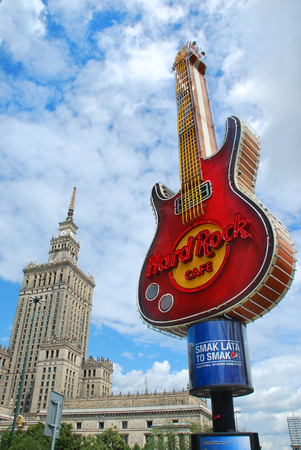 hard rock cafe: WARSAW,POLAND-JULY 15,2015:famous guitar-symbol of Hard Rock Cafe in the center of Warsaw and Palace of Culture and Science against cloudy sky