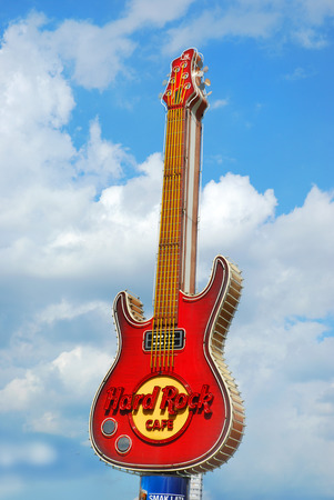 hard rock cafe: WARSAW,POLAND-JULY 15,2015:famous guitar-symbol of Hard Rock Cafe in the center of Warsaw against cloudy sky