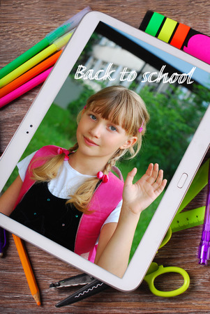 back to school wooden background with tablet pc displaying photo of happy school girl and text photo