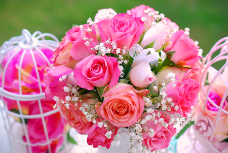rose bouquet: romantic style decoration with rose bouquet and metal cages in summer garden Stock Photo