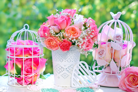 romantic style decoration with rose bouquet and metal cages in summer garden Stockfoto