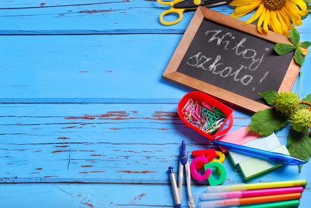 utiles escolares: frontera material escolar con el texto escrito en polaco nuevo a escuela en la peque�a pizarra en el fondo de madera azul