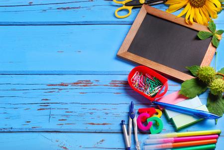 Frontera material escolar con la pequeña pizarra para escribir texto propio en el fondo de madera azul Foto de archivo - 44195320