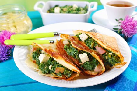 white cheese: plate of spinach ,bacon and feta filled pancakes Stock Photo