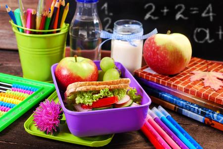 サンドイッチ、フルーツと弁当に飲み物が付いている学校の健康的な朝食
