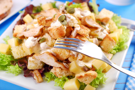 CHICKEN CAESAR SALAD: plate of ceasar salad with grilled chicken, cheese,croutons ,lettuce and garlic sauce Stock Photo