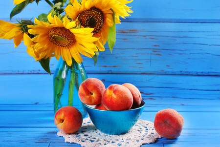 yellow flower tree: fresh ripe peaches in a bowl on blue wooden table and sunflowers in vase Stock Photo