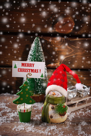 christmas  decoration with snowman figurine and christmas tree shaped greeting card holder with wishes on wooden background