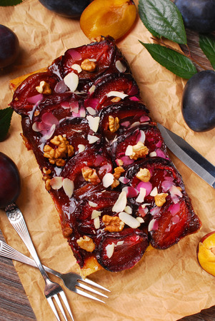homemade plum cake with walnuts and almond flakes on wooden table