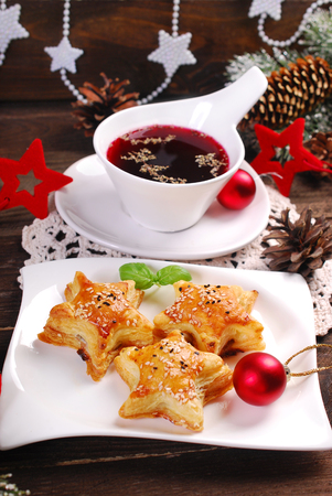 star shaped: star shaped puff pastries with mushrooms and cup of red borscht for christmas eve on wooden table Stock Photo