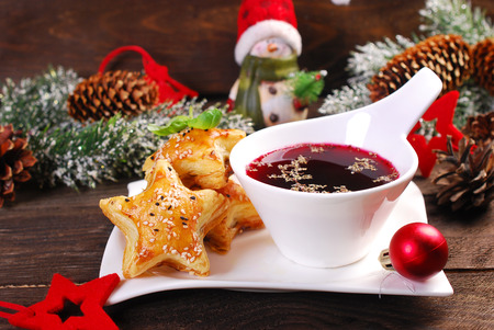 star shaped puff pastries with mushrooms and cup of red borscht for christmas eve on wooden table Reklamní fotografie