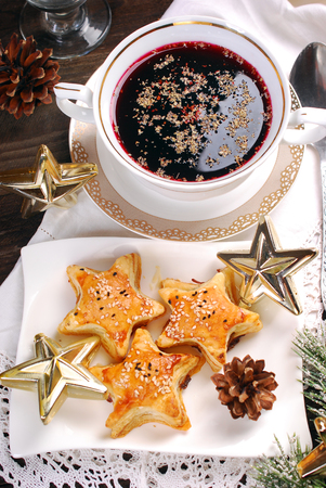 star shaped: star shaped puff pastries with mushrooms and cup of red borscht for christmas eve supper Stock Photo