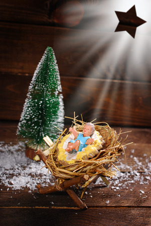 symbolic nativity scene with baby Jesus figurine lying on a hay in the manger on wooden background Stock Photo