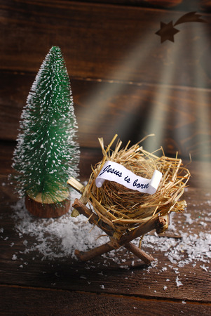 christ is born: symbolic nativity scene with inscription Jesus is born on  rolled paper lying on a hay in the manger instead of baby Jesus and  light rays of Bethlehem star on wooden background