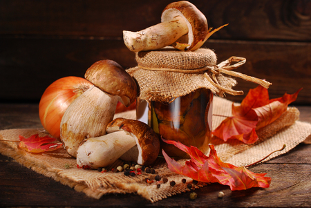 the fungus: some fresh porcini and jar of homemade pickled mushrooms on wooden background