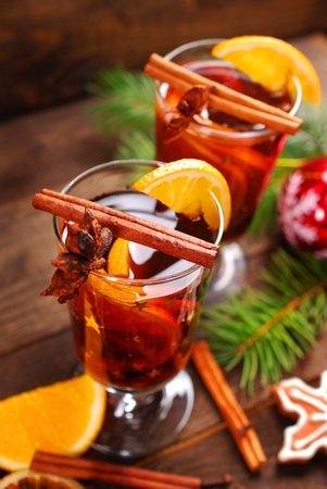 two glasses of mulled wine with spices for christmas on wooden background