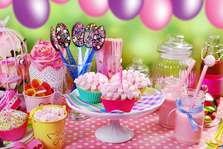 party table: mini marshmallow cupcakes ,chocolate spoons and other sweets  on pink birthday party table for kids