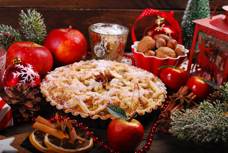 traditional apple pie with ingedients and decoration for christmas on wooden rustic table