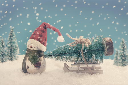 christmas time: winter scene with a snowman in a santa hat pulling a sled with christmas tree in vintage style Stock Photo
