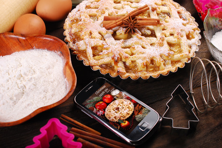 checking ingredients: baking christmas apple pie with ingredients on wooden table and checking recipe in smartphone Stock Photo