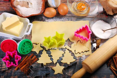cookie cutter: ingredients and utensils for baking christmas cookies on rustic wooden table Stock Photo