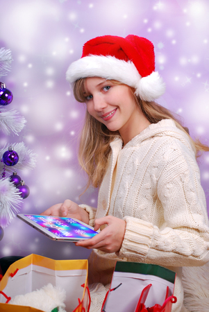 happy young girl sitting close to white christmas tree and opening perfect christmas gift with tablet pc photo