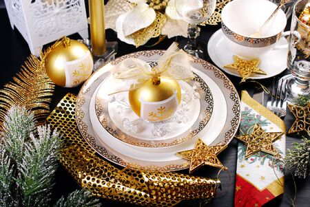 gold ornament: beautiful christmas table decoration in white and golden color on black table in glamour style