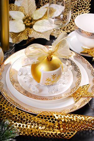 glamour: beautiful christmas table decoration in white and golden color on black table in glamour style